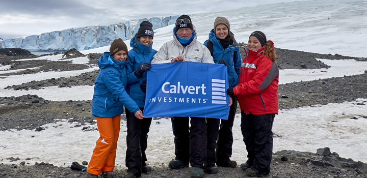 Calvert Investments - Polar explorer Rob Swan posing with the expedition members sponsored by Calvert, holding a Calvert Flag