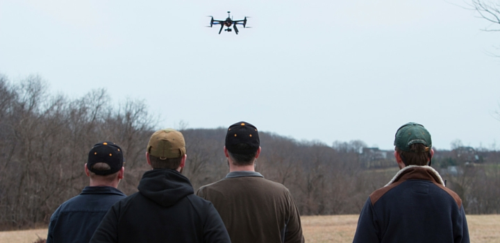 four men operating and watching a drone