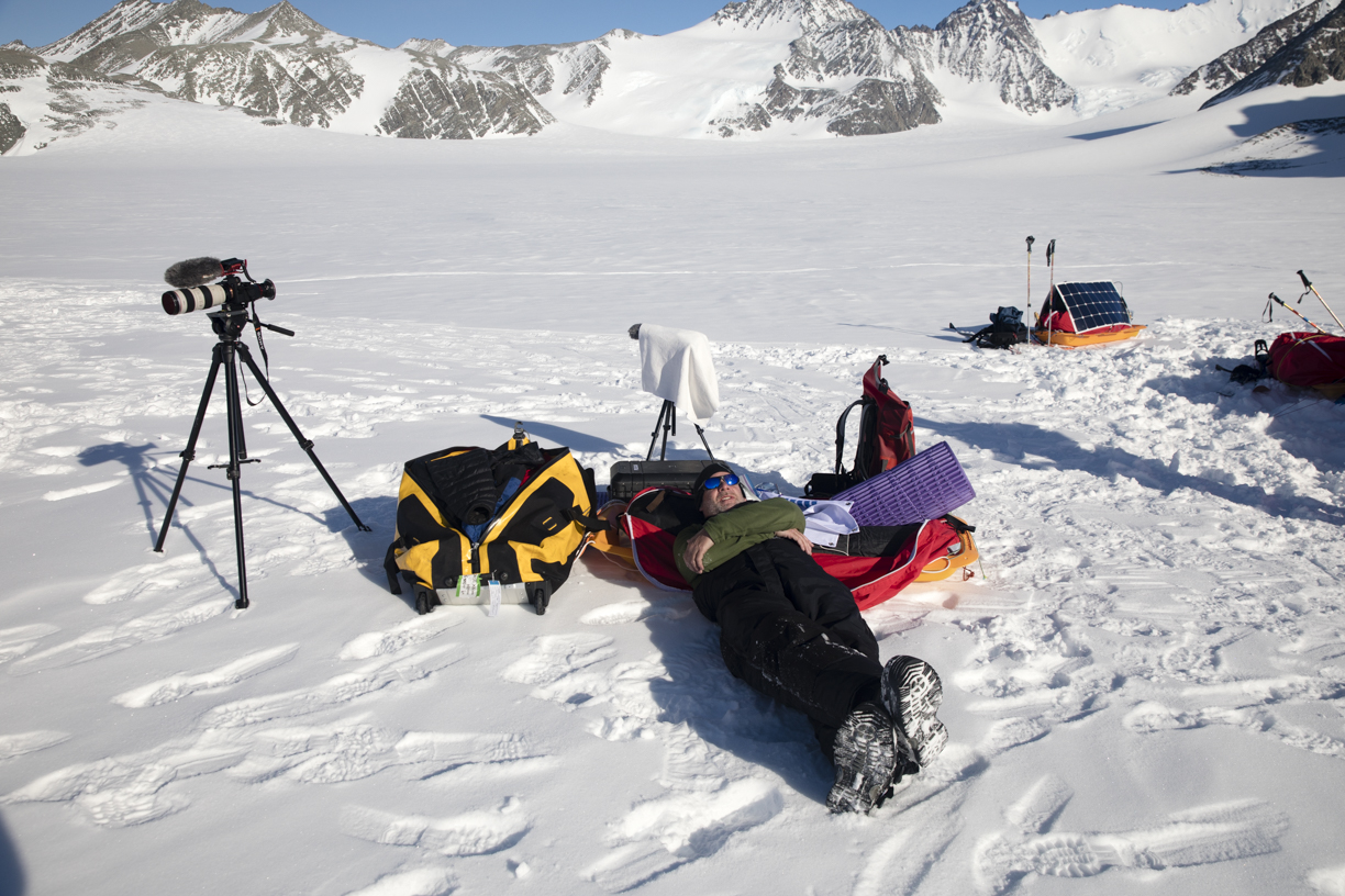 Mark Leisher resting with his camera gear in Anrctica